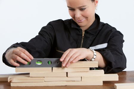 leveling: young adult woman leveling wooden construction Stock Photo