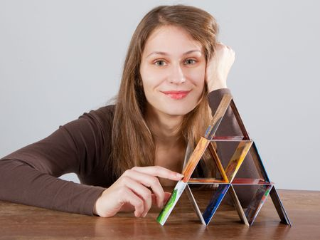 young woman building  credit card pyramid