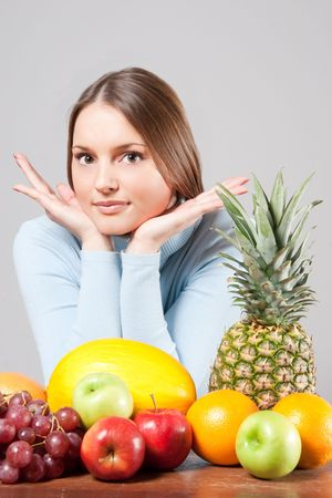 young adult woman with various colorful fruits Stock Photo