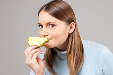 young adult woman smelling pineapple slice