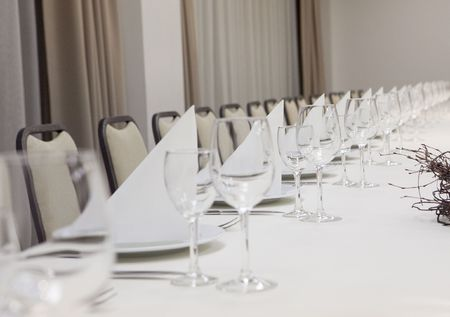 empty wine glasses on long restaurant table Stock Photo