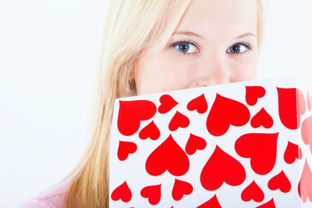 young adult blond woman holding big valentine postcard close to her eyes