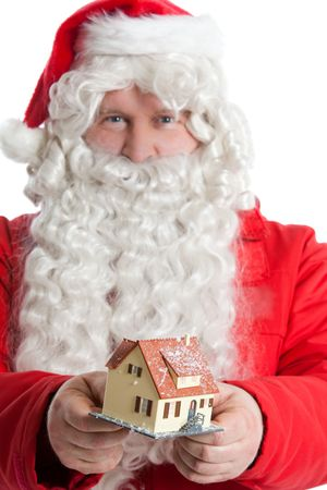 funny Santa Claus giving as small house a Christmas gift Stock Photo
