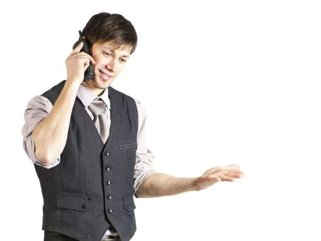 A handsome young businessman with vest and rolled-up sleeves smiles while using a cordless phone. Horizontal shot. Isolated on white.
