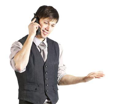 Ein handsome junge Geschäftsmann mit Vest und mehrstufigen Ärmel lächelt während der Verwendung eines schnurlosen Telefons. Horizontal gedreht. Isoliert auf weiß.