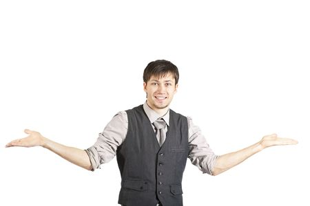 shrugs: A handsome young businessman in a vest and rolled up sleeves smiles at the camera and shrugs his shoulders. Horizontal shot. Isolated on white.