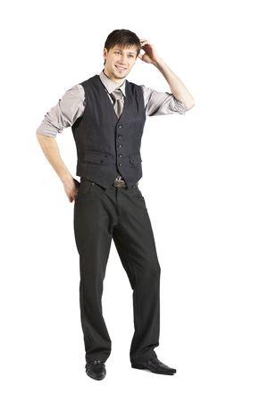 Gut aussehend jung kaufmann im Weste und rolled-Up Ärmel lächelt und Kratzer seinen Kopf. Vertikal gedreht. Isolated on White.