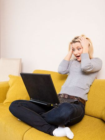 surprised young blond woman sitting on couch and looking at computer photo