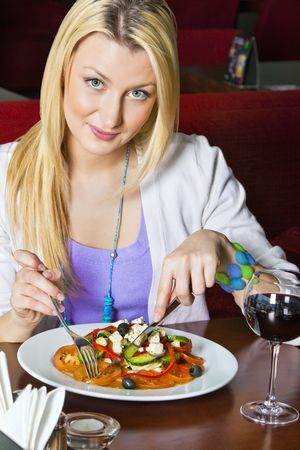 A young woman sitting in a restaurant. She is looking at the camera and smiling as she is cutting the food on her plate. Vertical shot. photo