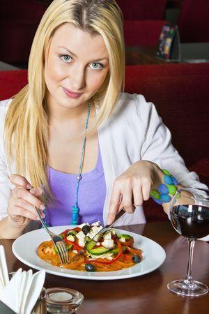 Eine junge Frau sitzen in einem Restaurant. Sie ist die Kamera betrachten und lächelnd, wie Sie das Essen auf ihrem Schild schneiden ist. Vertikale erschossen.