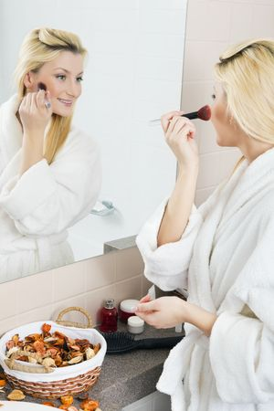 A young woman applies makeup in front of a bathroom mirror. Vertical shot.