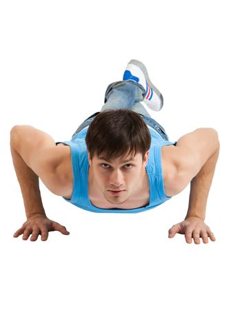 A handsome young man dressed in blue casual clothing making push-ups. Vertical shot. Isolated on white. Stock Photo
