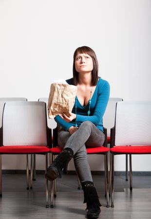 worried young woman sitting with crossed legs in front cheer row, looking up, holding paper bag Stock Photo - 6808746