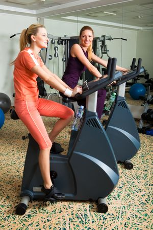 Two young women on exercise bikes in a gym. Vertical shot.