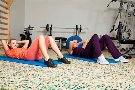 Portrait of two young, attractive women lying on floor and exercising in a health club. Horizontal shot. Stock Photo - 6874694