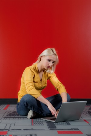 young blond woman sitting on floor and working with computer in red background, vertical shot