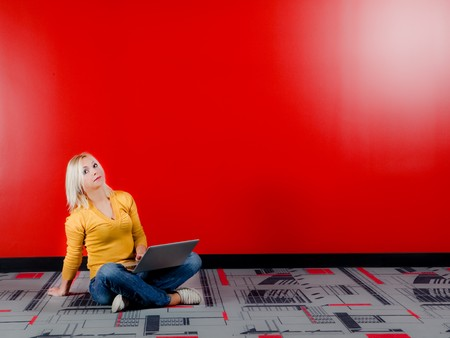 young blond woman sitting on floor and working with computer in red background, horizontal shot photo
