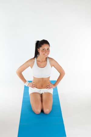knees bent: young woman exercising on blue carpet, vertical