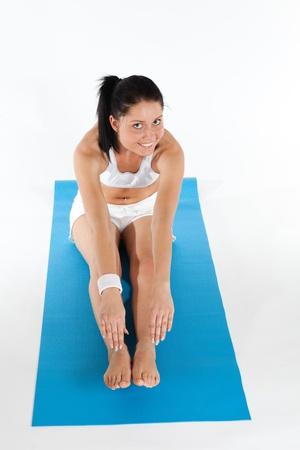 Young Woman doing Yoga auf hellblauem Teppich ausgelegt, vertikale