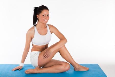 Young Woman doing Yoga auf hellblauem Teppich ausgelegt, horizontale Standard-Bild