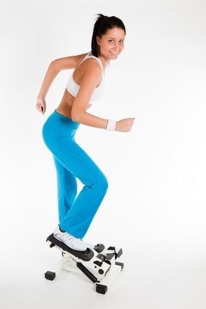 young woman exercising on stepper trainer, vertical photo