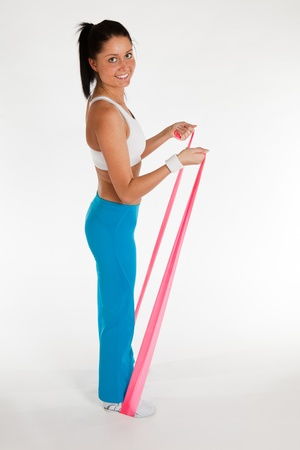 young woman exercising with rubber ribbon, vertical photo