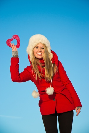 junge, blonde Frau im roten Wintermantel Holding Herzform Standard-Bild