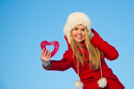 Junge, blonde Frau im roten Wintermantel Holding Herzform Standard-Bild - 12334393
