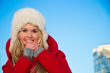 portrait of young blond woman in red winter coat holding hands close to face