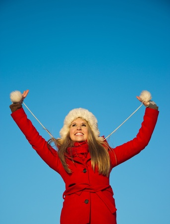 playful portrait of young blond woman in red winter coat holding hands up
