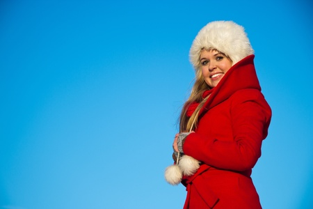 portrait of young blond woman in red winter coat and white fur hat
