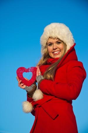 Junge, blonde Frau im roten Wintermantel Holding Herzform Standard-Bild - 12334399