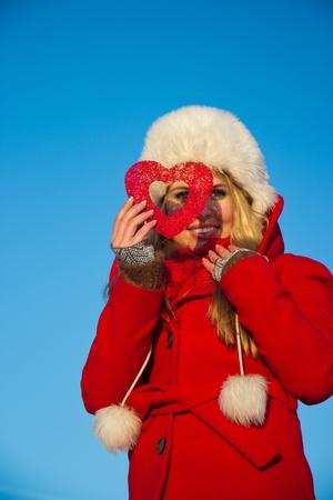junge blonde Frau im roten Wintermantel schaut durch Herz-Form Standard-Bild