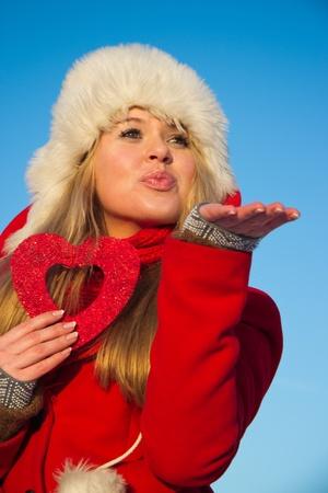 junge, blonde Frau im roten Wintermantel hält Herzform und Senden einer Luft Kuss Standard-Bild