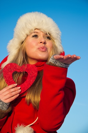 young blond woman in red winter coat holding heart shape and sending an air kiss