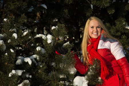 young blond woman in forest at winter time in red sport wear