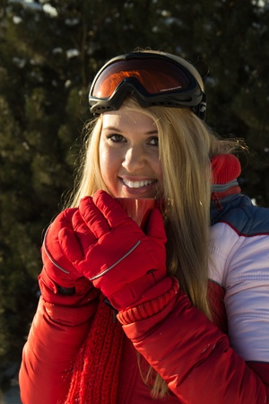 young blond woman holding a red cup close to face outdoors at winter Stock Photo