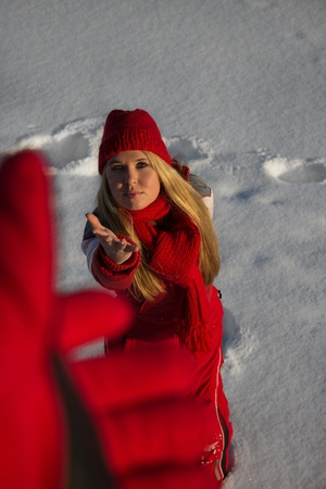 young blond woman in red sport wear reaching out hand for help in winter