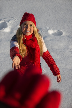 smiling blond woman reaching out hand, winter