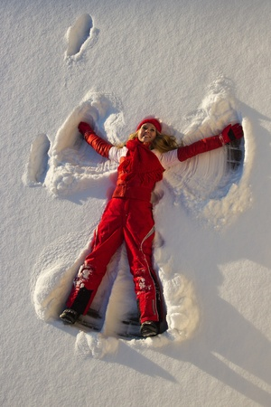 young blond woman making an angel on snow photo