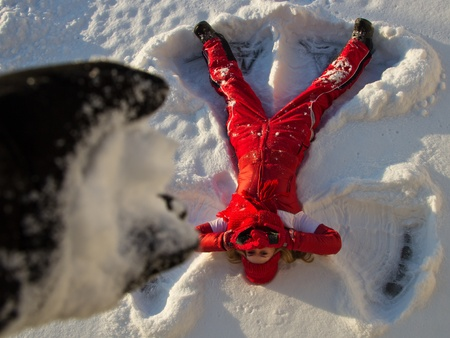 young woman lying on snow in angel form an covering face from snow attack