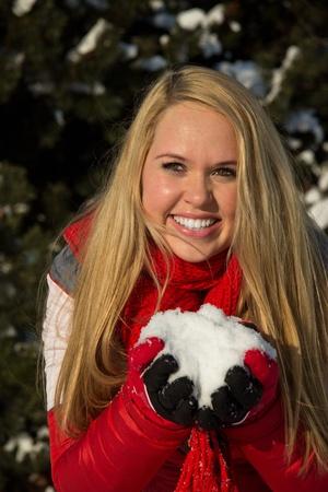 Blonde Frau hält lächelnd Haufen Schnee in den Händen Standard-Bild