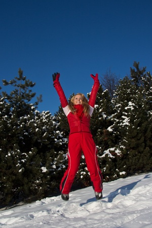 blond woman in red winter sport wear jumping in the air outdoors