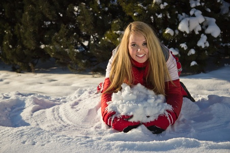 young blond woman building a snow pile Stock Photo