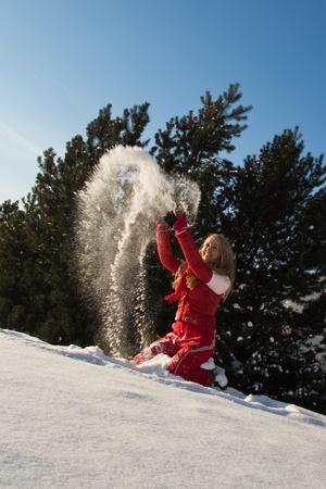 junge, blonde Frau wirft Schnee in der Luft Standard-Bild