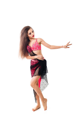 Beautiful girl dancing belly dance in red attire. A dancer performs an oriental tabla dance on a white background.