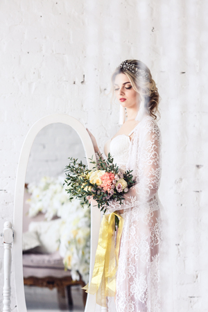 beautiful girl dressed in peignoir and underwear, stands near mirror and holds bouquet in her hands Standard-Bild