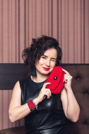 girl in black dress with handmade red bracelet, black knitted earrings and bag