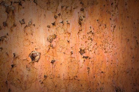 Vintage background of rusty metal sheet with exfoliated orange paint.