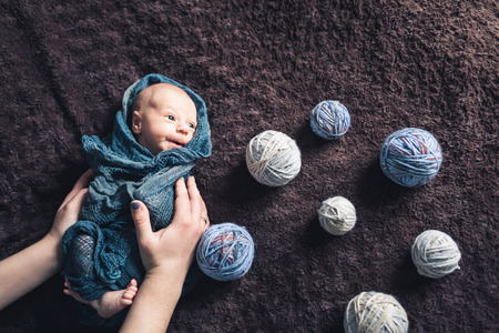Mom's hands hold baby wrapped in blanket amid tangles of thread. Beautiful concept of maternal love.
